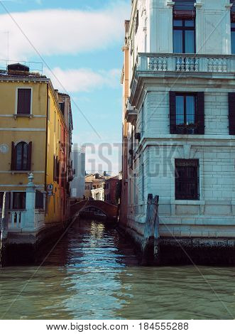 Looking down a small canal in Venice from a waterway junction showing old buildings and blue sky