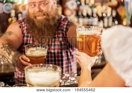 Focus on close up glass of appetizing beer. Female taking it from happy fat bartender in boozer