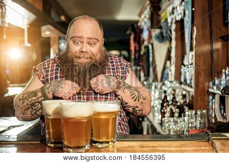 Bearded man expressing happiness while looking at big glasses of beer in dramshop