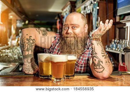 And what is it. Portrait of bearded man expressing wonder while locating at counter in bar