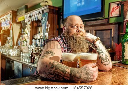 It is my drink. Portrait of fat male demonstrating surprise while hugging glasses of alcohol in pub