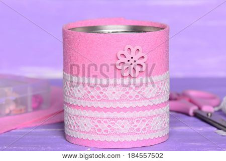 Felt and ribbon recycled tin can. Recycling tin cans into holder to contain pens, pencils, markers and other office supplies. Thrifty, quick and easy recycled home crafts concept. Closeup