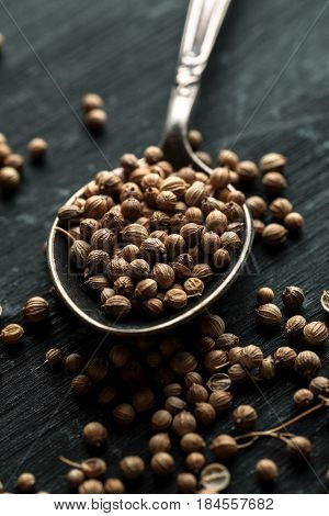 Coriander Dry Seeds In Metal Spoon On A Black Wooden Table