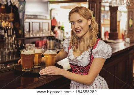 Portrait of woman showing happiness while putting tray with glasses of beer on counter in bar