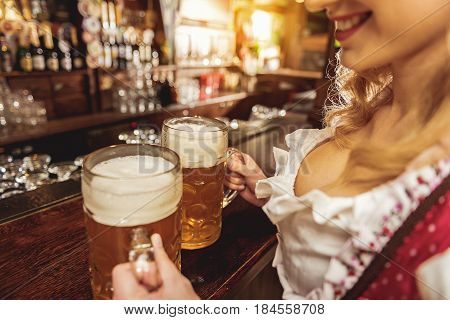 Focus on close up arms of outgoing young female keeping cups of alcohol beverage in boozer