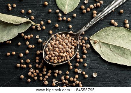 Coriander Seeds In Metal Spoon And Dry Bay Leaves On A Black Wooden Table, Selective Focus