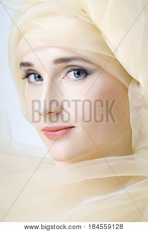 Beautiful young woman with clear skin and blue eyes with scarf on head
