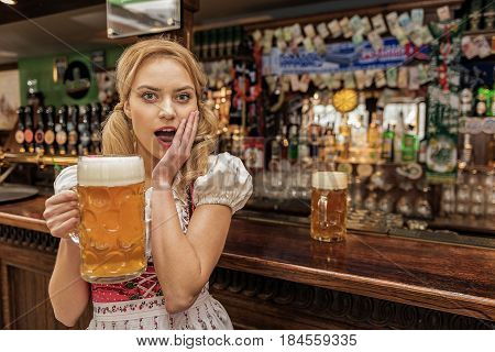 Portrait of astonishing young woman keeping alcohol beverage in tap-room