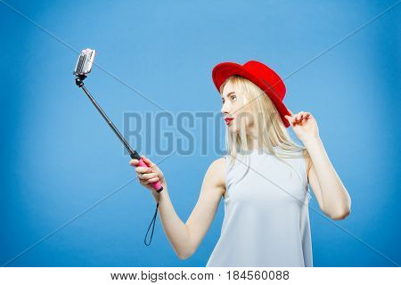 Amazing Blonde with Sensual Lips and Red Hat Photographing Herself. Smiling Girl Using Selfie Stick to Take a Photo on Blue Background. Horizontal.