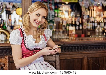 Portrait of woman expressing happiness while looking at mobile in pub
