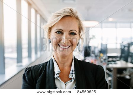 Close up portrait of successful mature businesswoman standing in office. Caucasian female executive in suit looking at camera and smiling.