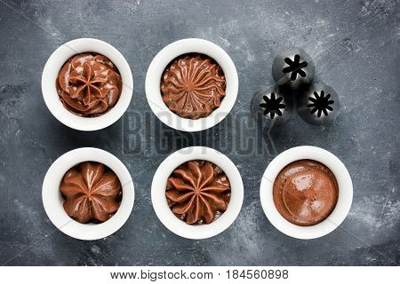 Chocolate frosting swirls and various metal confectionery nozzles for decorating capcasks top view
