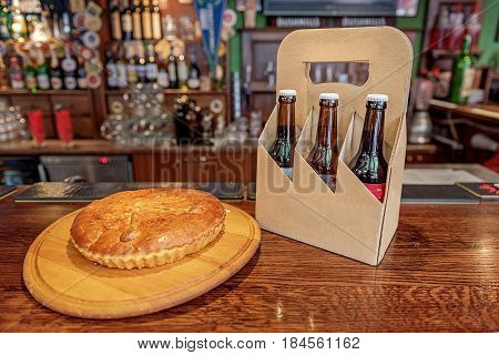 Fried pie and bottles of beer locating on bar surface in alehouse