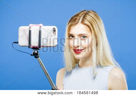 Amazing Girl with Long Hair and Red Lips Photographing Herself by Smartphone in Studio. Pretty Blonde is Grimacing While Taking a Photo Using Selfie Stick on Blue Background, Closeup.