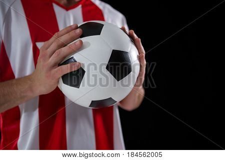 Mid-section of football player holding football with both hands against black background