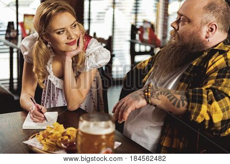Attractive smiling waitress telling with calm obese male in pub