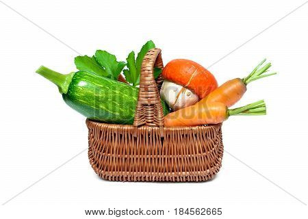Carrots zucchini and pumpkin in the basket. White background - horizontal photo.