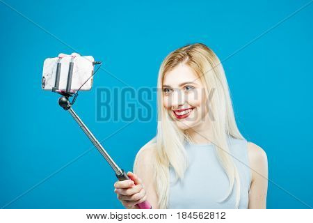 Smiling Sensual Girl Using Selfie Stick to Take a Photo on Blue Background. Cute Blonde with Sensual Lips Photographing Herself. Woman Portrait in Studio.