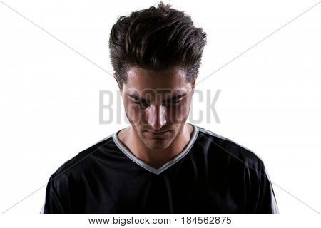 Upset football player looking down against white background