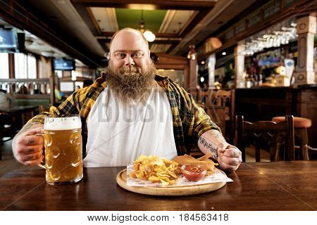 Portrait of bearded obese man expressing pleasure. He drinking alcohol and eating food in dramshop