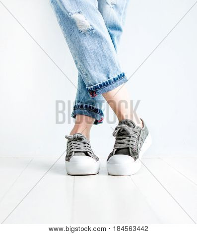Female shoes sneakers legs in jeans on a white background