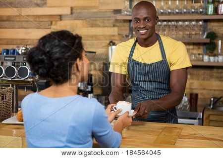 Portrait of happy male barista serving coffee to customer in coffee shop