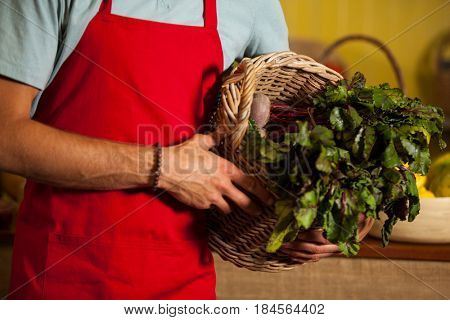Mid section of male staff holding leafy vegetables in basket at organic section of supermarket
