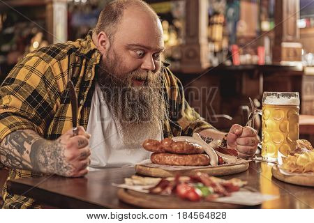 This is appetizing dish. Bearded overweight male demonstrating hunger while eating sausages and alcohol in boozer