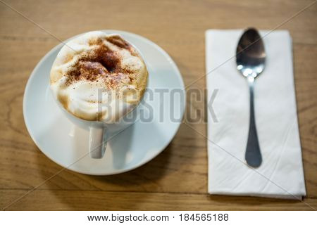 Close-up of coffee cup with creamy froth on table in cafeteria