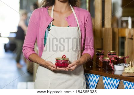 Mid-section of staff holding jar of maraschino cherry in market