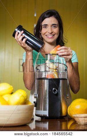 Portrait of smiling shop assistant preparing juice at health grocery shop
