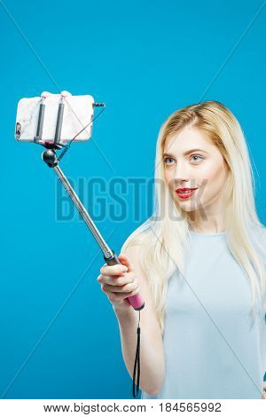 Smiling Girl in Dress Photographing Herself by Smartphone in Studio. Portrait of Blonde Taking Photo Using Selfie Stick on Blue Background.