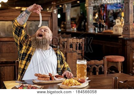 This delicious meal. Outgoing bearded overweight male eating sausages with arms in boozer