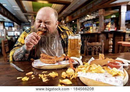 I want more and more dish. Focus on fat male expressing gluttony while tasting frankfurters in pub