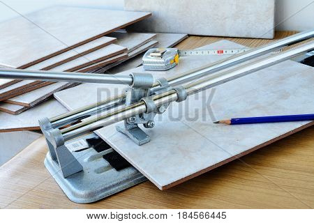 Cutting ceramic tiles with manual tile cutter machine DIY home remodeling.