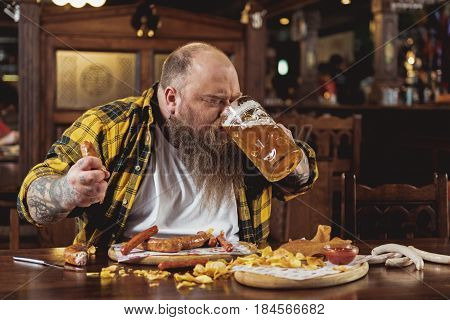 Obese male expressing gladness while tasting mug of cold foamy alcohol drink in pub