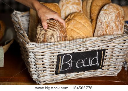 Hand of female staff holding breads at counter in bakery shop