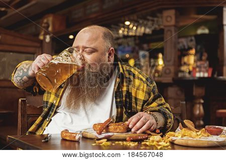 Bearded fat man demonstrating pleasure while drinking glass of beer and eating frankfurters in boozer