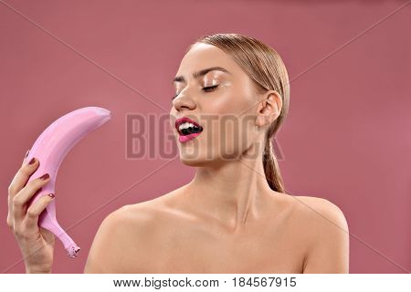 Get freaky with my fruit. portrait of happy young woman holding color banana while standing with closed eyes, isolated on pink background