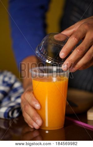 Male staff putting straw in a glass at supermarket