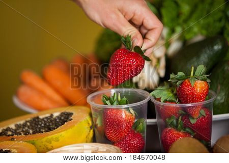 Hand of male staff holding strawberry in supermarket
