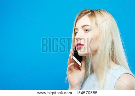 Side View of Cute Blonde in Dress Calling to Somebody Using her Smartphone on Blue Background. Attractive Girl with Mobile in Studio. Technology Concept.