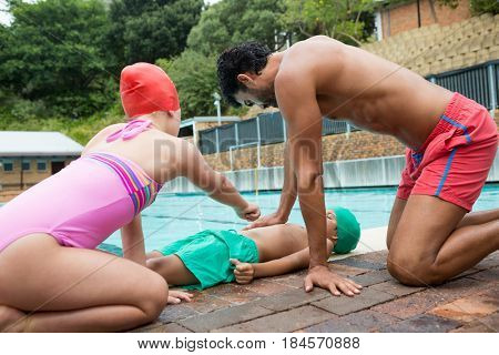 Lifeguard assisting unconscious boy while interacting with girl near swimming pool