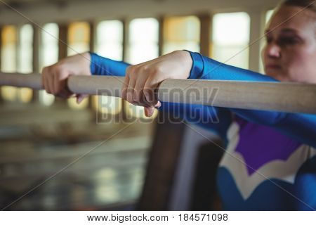Close-up of female gymnast practicing gymnastics on the horizontal bar in the gymnasium