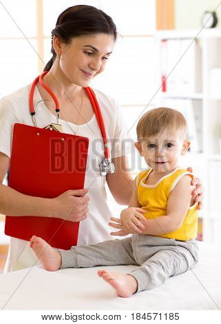 Kid boy and affable female doctor in medical office