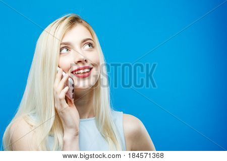 Happy Joyfull Woman is Talking by Mobile Phone and Smiling on Blue Background. Portrait of Blonde with Long Hair with Smartphone in Studio. Communication Concept.