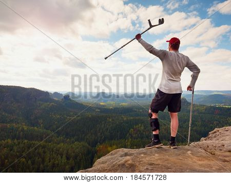 Happy Tourist With Forearm Crutch Above Head Achieved Mountain Peak. Hiker With Broken Knee In Immob