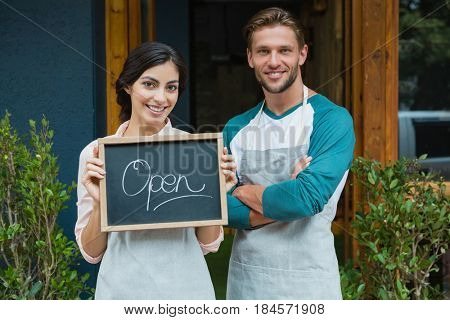 Portrait of smiling waiter and waitress standing with chalkboard outside the cafe