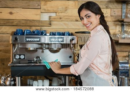 Portrait of waitress cleaning coffeemaker machine in cafe