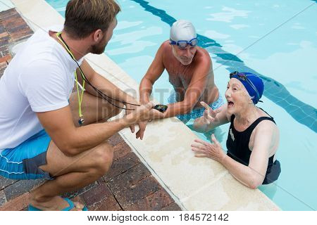 Swim coach interacting with senior couple at poolside